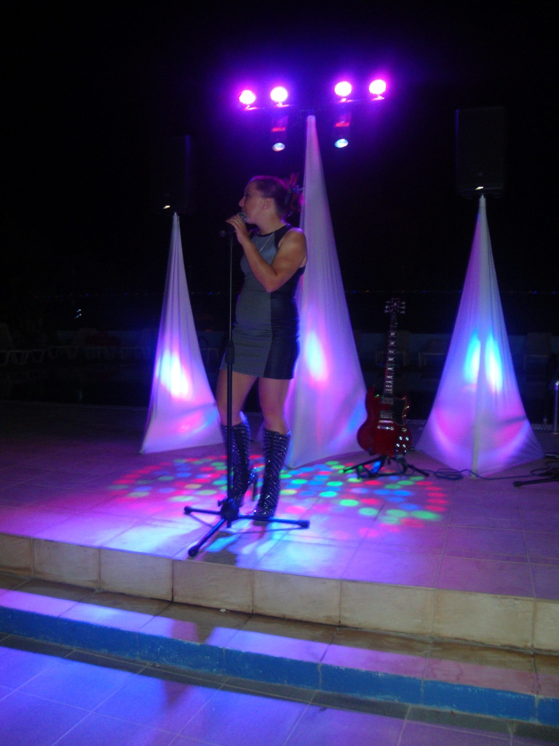Speakers on stands with covers and uplighters and a large T b-bar with spotlights and effects